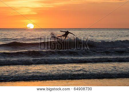Surfer enjoying sunset in Playa Negra, Costa Rica