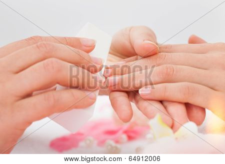 Beautician Filing The Nails Of Woman
