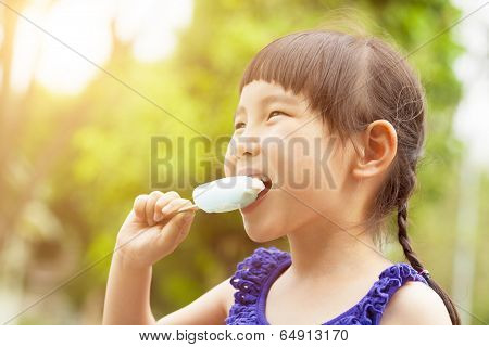 Happy Little Girl Eating Popsicle At Summertime With Sunset