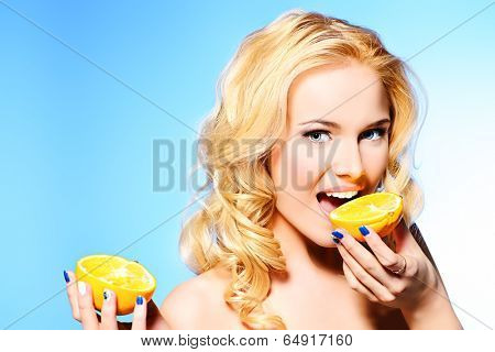 Portrait of a beautiful young woman eating fresh orange.