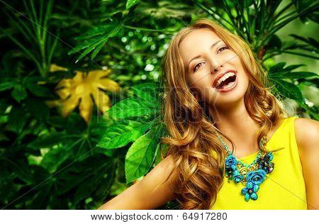 Beautiful laughing young woman among the tropical plants. Vacation. Tropics. Fashion shot.