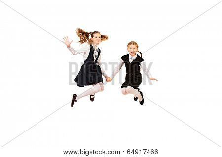 Two ten years girls in a uniform jumping for joy. Isolated over white.