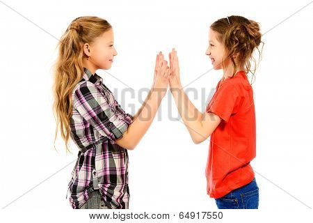 Two smiling girls standing together and playing. Isolated over white.