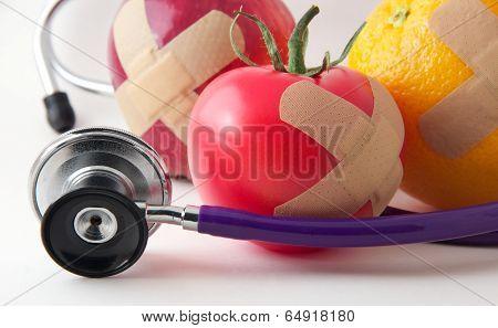 Closeup Bandaged Apple, Tomato, and Orange with Stethescope