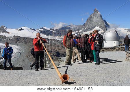 Swiss man blowing traditional alpine horn on Matterhorn mountain