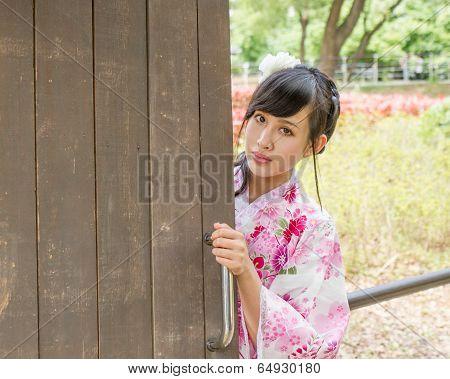 Asian Woman Wearing A Kimono In Japanese Garden
