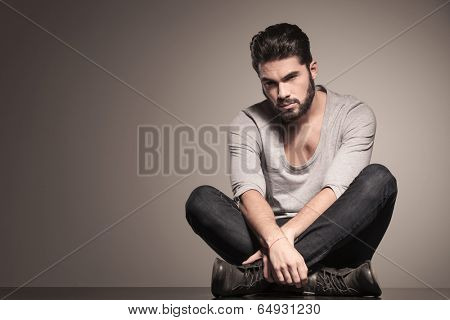 serious bearded fashion man sits in yoga position on the floor
