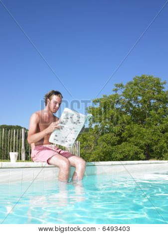 Man Reading At Edge Of Swimming Pool
