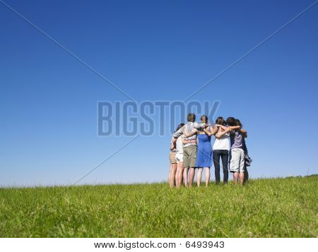 Group Of People In Huddle In Field
