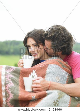 Couple Snuggling And Drinking Tea
