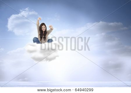 Woman looks straight ahead as she celebrates in front of her laptop against beautiful blue sky with clouds