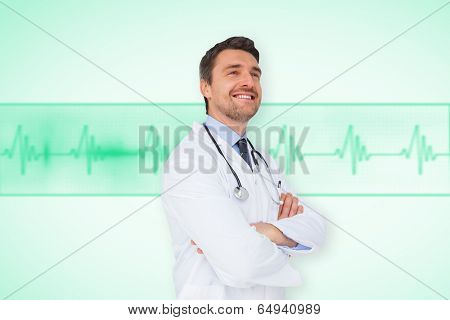 Handsome young doctor with arms crossed against green medical background with ecg line
