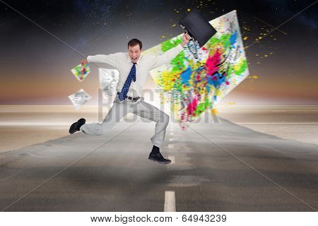 Cheerful jumping businessman with his suitcase against road leading out to the horizon