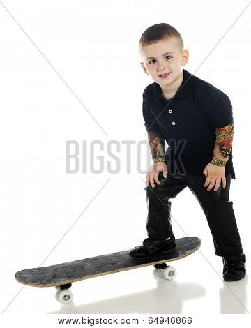 A happy preschooler with tattooed arms and black leather pants standing with one foot on his skateboard, ready to ride.  On a white background.