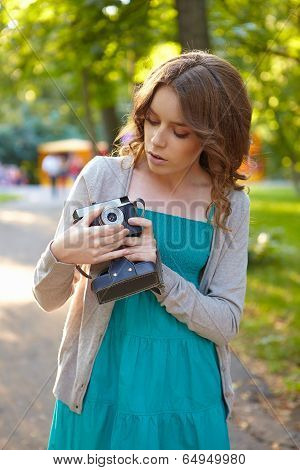 Young Woman Uses Film Photocamera.