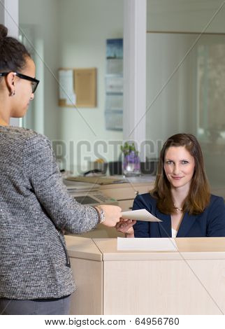 Clerk Is Handing Over A Document To A Customer