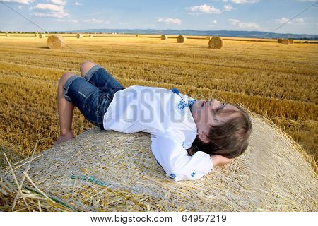 small rural girl on the straw after harvest field with straw bales