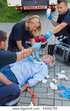 Paramedics examining unconscious senior man lying on ground