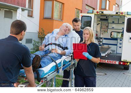 Emergency team assisting injured elderly man lying on stretcher outdoors