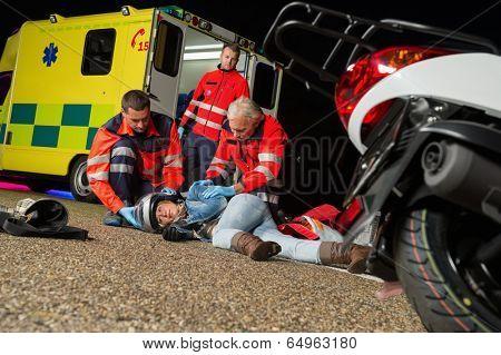 Paramedics helping injured motorcycle woman driver lying on road night