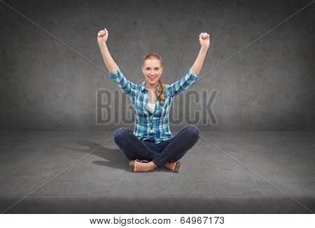 happiness and people concept - smiling young woman in casual clothes sitiing on floor