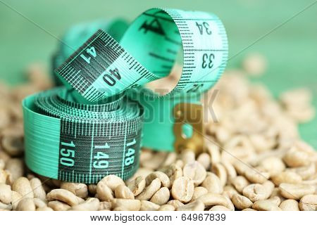 Raw green coffee beans and measuring tape, on color wooden background. Concept of weight loss
