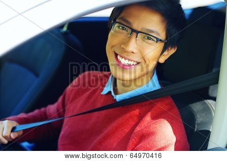 Young asian man fastening seat belt