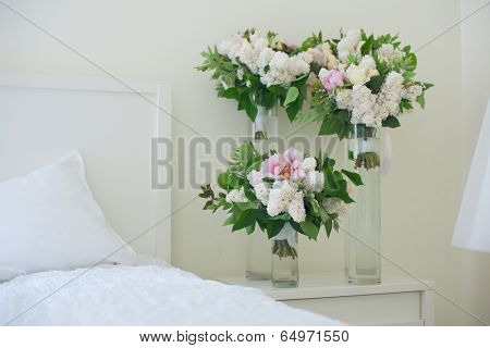 Flowers in vase on bedside table in bedroom. Fresh design.