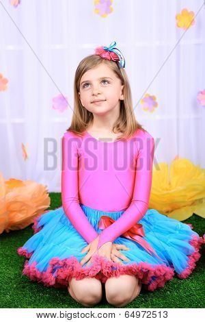 Beautiful small girl in petty skirt on decorative background