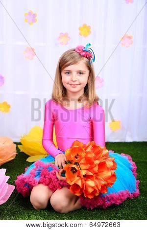 Beautiful small girl in petty skirt holding flowers on decorative background