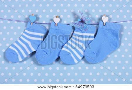Baby Boy Nursery Blue Socks And Butterfly Hanging From Pegs On A Line