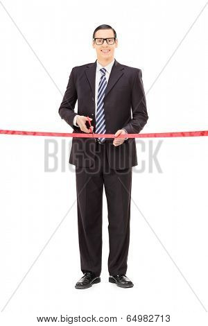 Full length portrait of a young businessman cutting a red tape isolated on white background