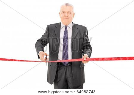 Mature businessman cutting a red tape isolated on white background