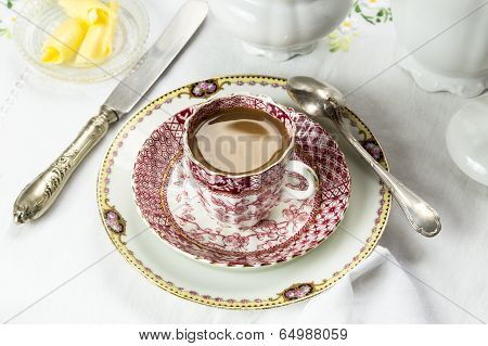 Antique porcelain breakfast setting with milk coffee on white cloth