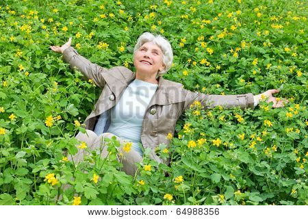 Happy Beautiful Elderly Woman Sitting Arms Outstretched On A Glade Of Yellow Flowers In Spring