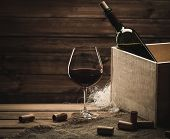 foto of merlot  - Bottle and glass of red wine on a wooden table  - JPG