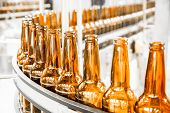 stock photo of malt  - Beer bottles on the conveyor belt brewery