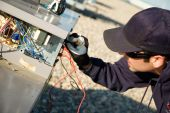 foto of hvac  - Worker testing a roof top air exchange units operation.