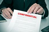 stock photo of private detective  - a man wearing a suit showing a document with the text confidential written in it - JPG