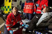 stock photo of stretcher  - Paramedics assisting injured motorcycle man driver on stretcher at night - JPG