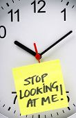 foto of time flies  - Yellow Sticky note with the phrase Stop Looking At Me stuck to the face of an office clock as a concept for watching the clock - JPG