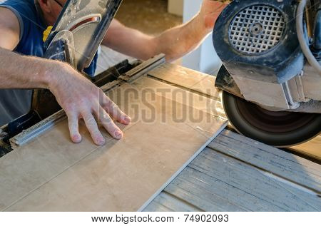 A wet saw cutter is being used to cut floor tile