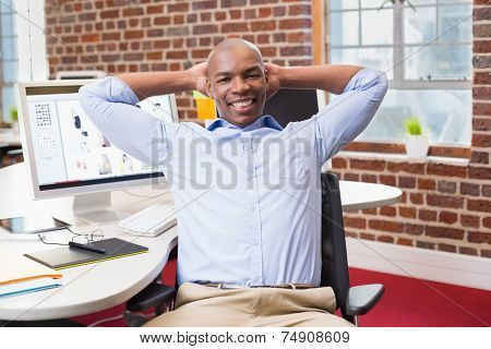 Portrait of young businessman sitting with hands behind head at office desk