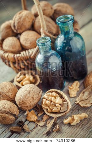 Walnuts In Basket And Nuts Tincture Or Oil On Old Table