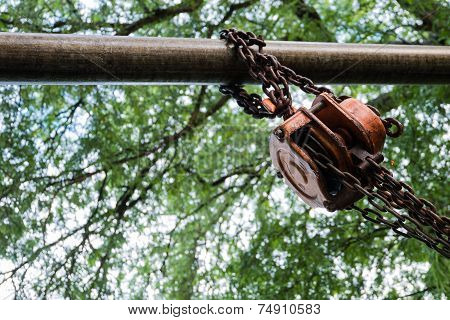 Orange Industrial Hook Chains Attached To A Pulley And Green Tree Background