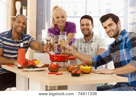 Happy young companionship clinking glasses around dinner table, smiling, looking at camera.