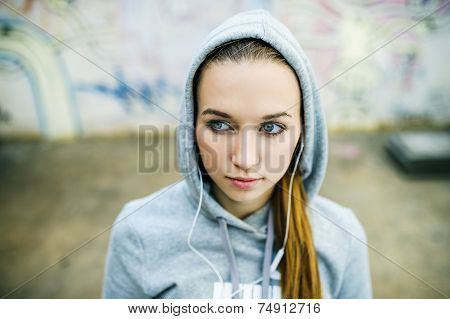 Teenage girl with hood on listening to music