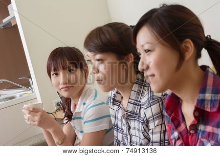 Group of Asian women chat and watch tv in the living room.