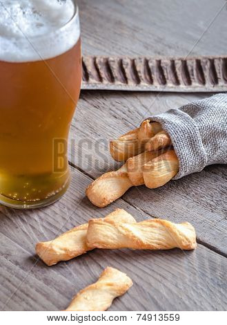 A Glass Of Beer With Breadsticks
