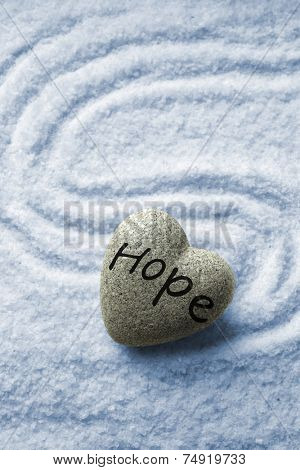 Grey zen stone in shape of heart, on blue sand background